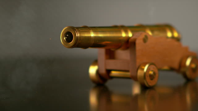 MACRO, DOF: Vintage brass toy cannon shoots a small cannonball across the room.