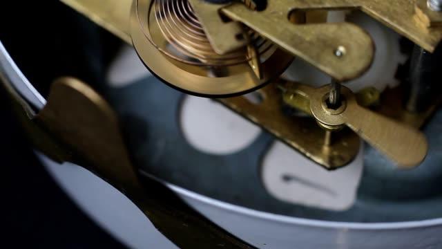 Vintage clock mechanism working, closeup shot with soft focus. Close up of a internal clock. Watch Gears Movement Macro.