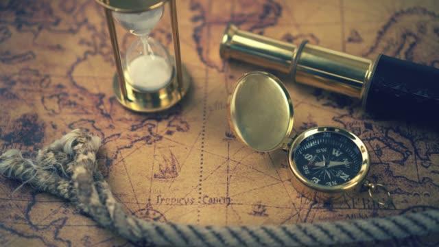 vintage kompass, fernrohr und anderen nautischen geräten auf alte weltkarte - kartographie stock-videos und b-roll-filmmaterial
