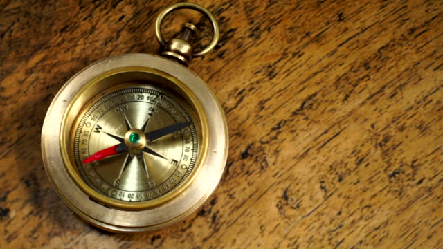 Vintage Compass Vintage brass compass on a wooden table, close up. compass stock videos & royalty-free footage