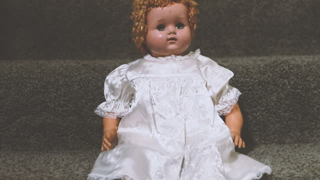 Vintage Doll in White Dress on Stairs