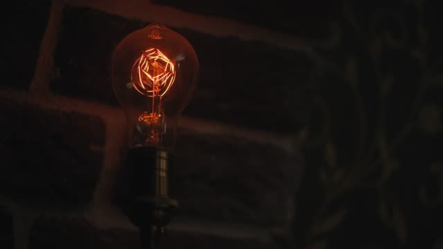 Vintage filament bulb lighting up Vintage bulb lighting up against brick wall low lighting stock videos & royalty-free footage