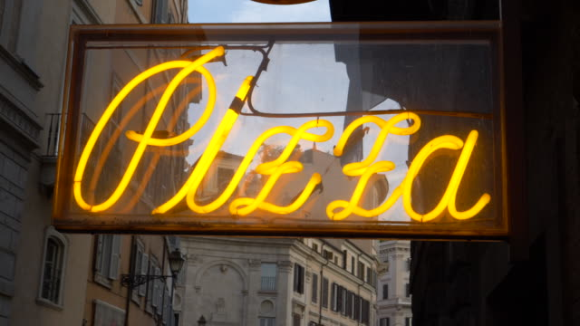 CLOSE UP: Vintage lettering glowing outside of a traditional pizza shop in Rome.