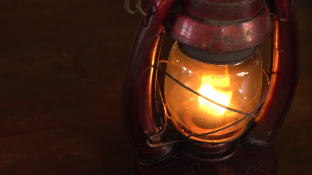 Vintage oil lamp antique stands on the table in the dark. video