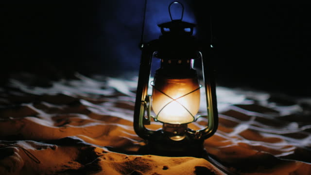 Vintage oil lamp standing on the sand, shines in the dark video