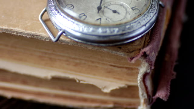 Vintage pocket watch next to the old faded book, Vintage Antique pocket watch on the background of old books.Vintage pocket watch next to the old faded book, hot pockets stock videos & royalty-free footage