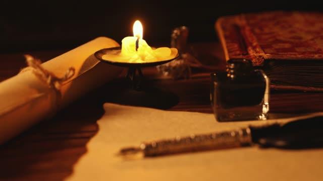 penna d'penna vintage e inkwell su carta vecchia pergamena a lume di candela - candeliere video stock e b–roll