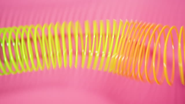 vintage retro abstract background. rainbow coloured spring moves across a pink background in a wave like pattern. slinky toy. rainbow spiral spring motion wave a bright beautiful background. - molla video stock e b–roll