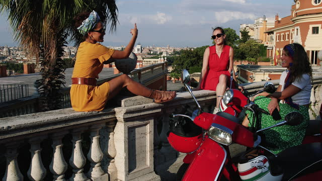 Vintage scooter riding: girl friends with motorbikes in the center of Rome