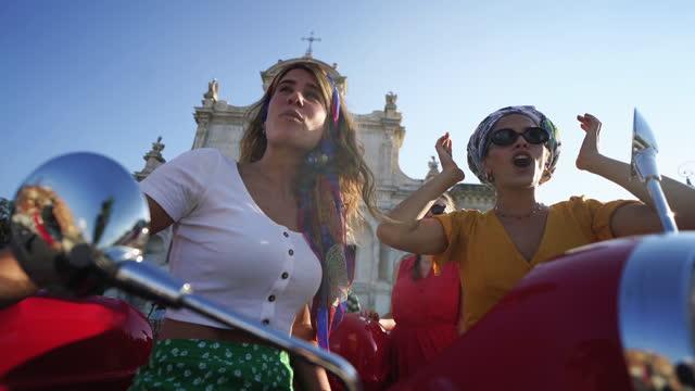 vídeos de stock e filmes b-roll de vintage scooter riding: girl friends with motorbikes in the center of rome - amizade feminina