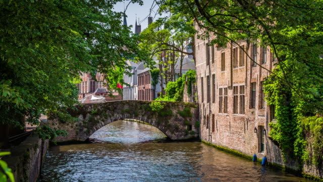 vintage stone bridge over a canal in bruges, belgium - bruges video stock e b–roll