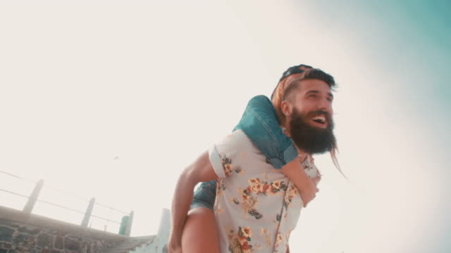 Vintage style image of a hipster guy piggybacking his girlfriend video