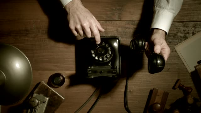 Vintage style office worker dialing a phone number 1950s style office worker dialing a phone number in the vintage office at night using a rotary dial telephone, noir movie style, flat lay desktop 20th century stock videos & royalty-free footage