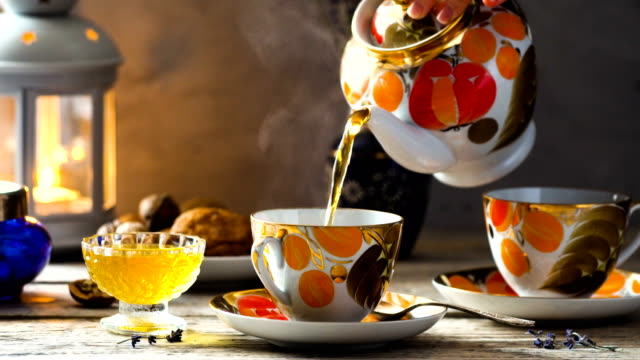 vintage tea party tea time, tea is pouring from the teapot in old fashioned cups of orange and gold colors on wooden desk with candle and honey mug stock videos & royalty-free footage