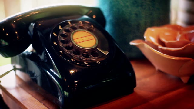Vintage telephone on a wooden table near the window.