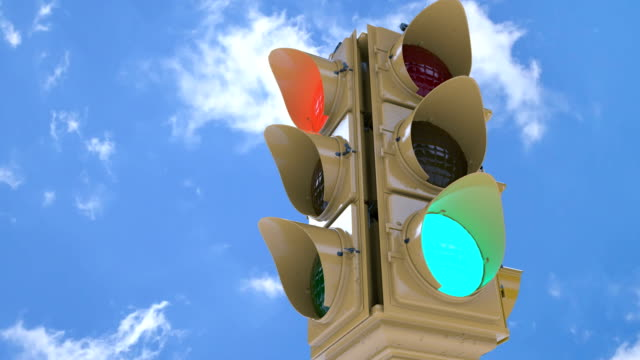 Vintage traffic lights against sunny blue sky, intersection, road traffic