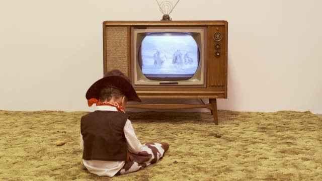 Vintage TV and Little Boy Cowboy A period correct 1960's television displaying a cowboy scene on the screen (not simulated) with a little boy dressed as a cowboy watching the screen. horseback riding stock videos & royalty-free footage