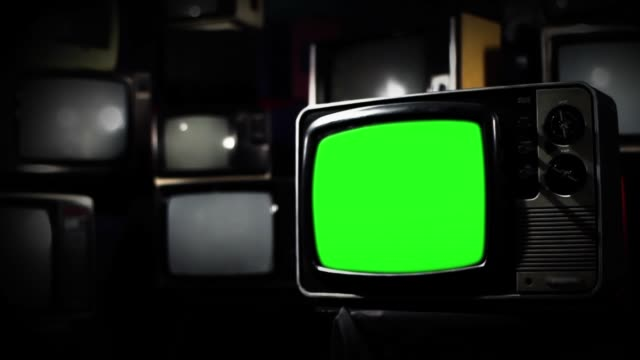 Video Vintage TV with Green Screen Over Many Old Tvs. Blue Steel Tone. Zoom Out.