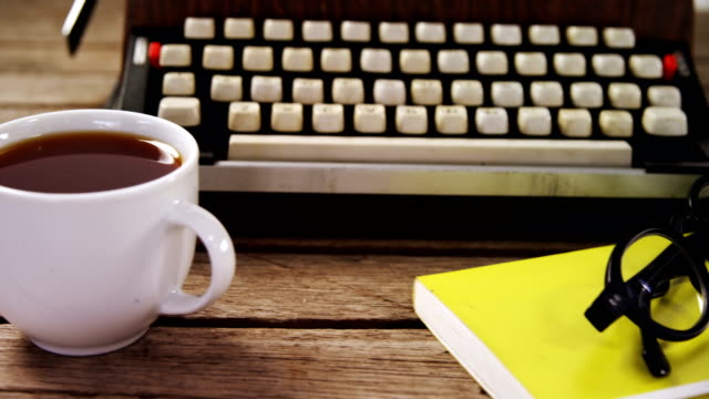 Vintage typewriter, diary, black coffee and spectacles on wooden table 4k video
