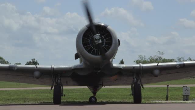 vidéos et rushes de vintage war war 2 états-unis navy warbird airplane startup sur l'aérodrome - hélice pièce mécanique