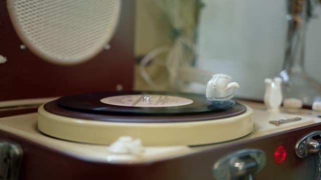 un disco in vinile che accende un lettore di vinile, pan shot - disco audio analogico video stock e b–roll