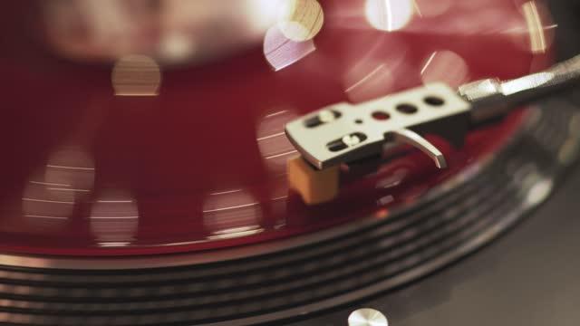 il lettore di vinile tramonto sfondo bokeh illumina la città serale. la mano della ragazza posiziona la piastra in vinile rosso rotante dell'ago. piatto rotante grammofono incluso. luci di natale. popular disco trends anni '70, '80, '90 - disco audio analogico video stock e b–roll