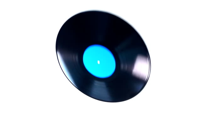 Vinyl record flies and rotates on a white background in slow motion video