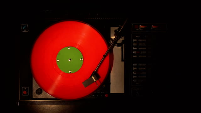 vinyl record pleer. plays song from an old turntable 4k top view. - disco audio analogico video stock e b–roll