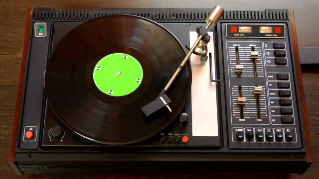 vinyl record pleer. plays song from an old turntable 4k top view. - giradischi video stock e b–roll