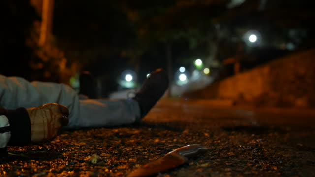 A violence male victim body with a bloody hand lying on the asphalt ground of a street at night in Medellin Colombia, Latin America, a bloody big knife is thrown and a person runs away