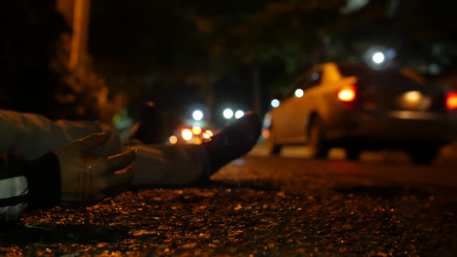 a violence male victim body with a bloody hand lying on the asphalt ground of a street at night in medellin colombia, latin america, a car drives by in the blurry background - убийство стоковые видео и кадры b-roll