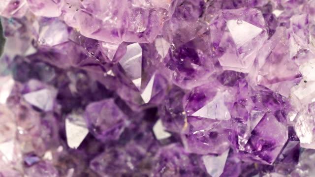 violet amethyst gemstone mineral rotating close up - кристалл стоковые видео и кадры b-roll