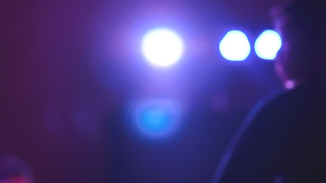 バイオレット色の人々 とステージ上でスポット ライトのコンサート - 在庫ビデオで注意を払って立っている. - オペラ点の映像素材/bロール