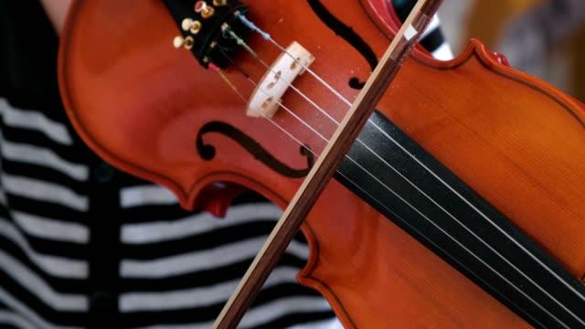 Violin in boy's hands.