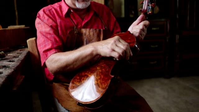 vídeos de stock e filmes b-roll de violin maker in his workshop - manual