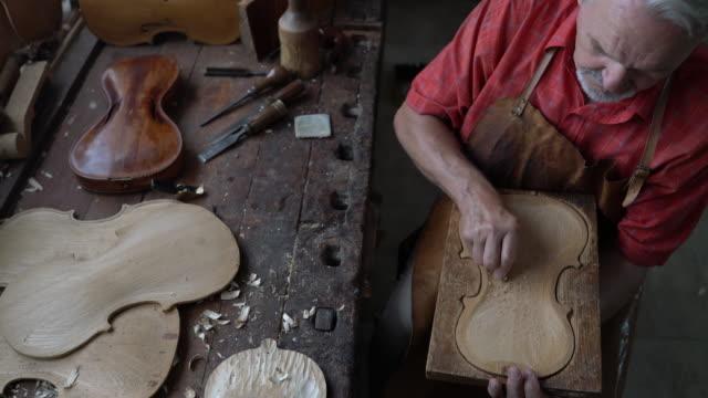 violin maker in his workshop - warsztat filmów i materiałów b-roll