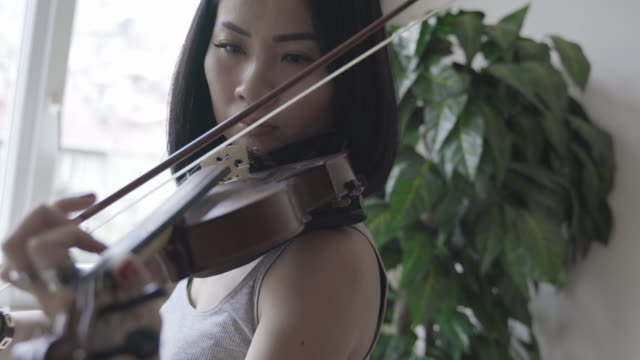 Violinist Asian woman playing violin at home Violinist Asian woman playing violin at home classical concert stock videos & royalty-free footage