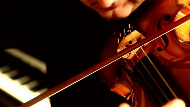 violinista suona il violino in parte anteriore di pianoforte - top nero video stock e b–roll