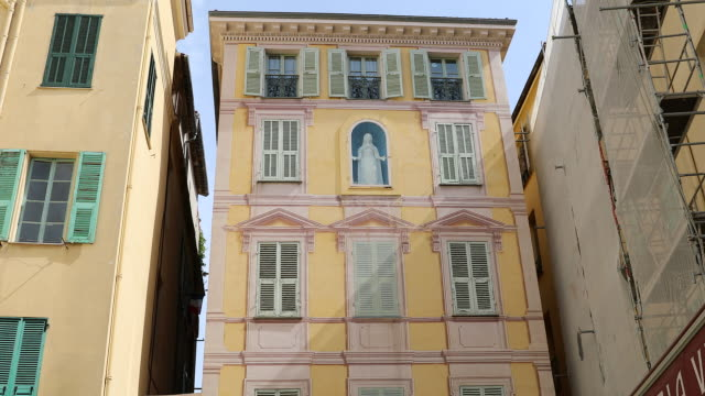 Virgin Mary On The Facade Of A House In Menton France Virgin Mary Sculpture On The Typical Colorful Facade Of A House In The Old Town Of Menton, Place Du Cap On The French Riviera, France Europe, Close Up View - DCi 4K Resolution french architecture stock videos & royalty-free footage