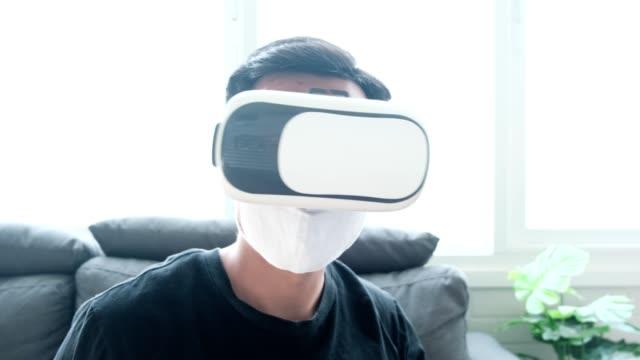 Virtual reality putting on VR headset immerse within the function Asian man interacting wearing facemask during quarantine social distancing lockdown augmented reality futuristic