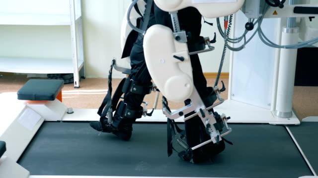 患者のリハビリテーションのための仮想現実シミュレータ。ウォーキングトラックで足を訓練する障害者男性の側面図 - 回復点の映像素材/bロール