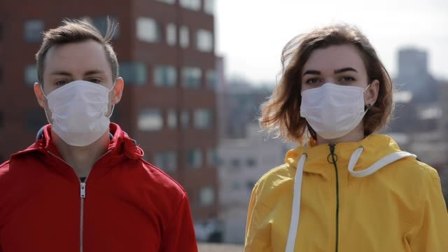 vídeos de stock e filmes b-roll de virus epidemic covid-19 is finish in a city, woman and man take off surgical masks - remover