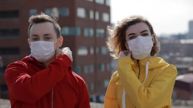 virus epidemic is finish in a city, woman and man take off surgical masks from faces - убирать стоковые видео и кадры b-roll