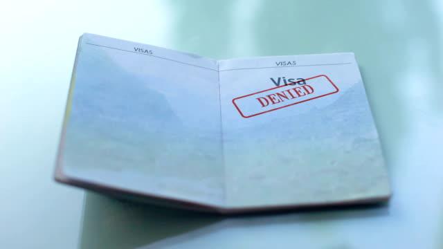 vídeos y material grabado en eventos de stock de visa negada, mano del oficial de aduanas estampa sello en el pasaporte, viajar al extranjero - pasaporte y visa