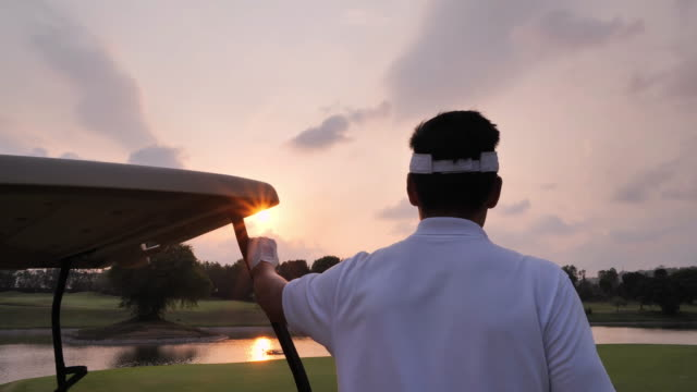 Vision concept. Successful businessman standing on the golf course and looking over sunset.Sports Cinemagraphs
