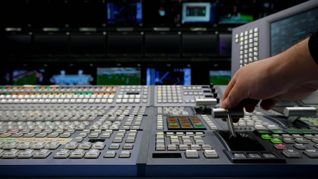 Vision Switcher Studio Director broadcast video mixer operation - Close-up of hand. Hands of a cinematographer who worked on the vision mixer, switch the TV panel.