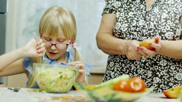 Visiting grandmother. A 6 year old girl eats a salad, next to an elderly woman is cleaning an apple with a knife for her beloved granddaughter video