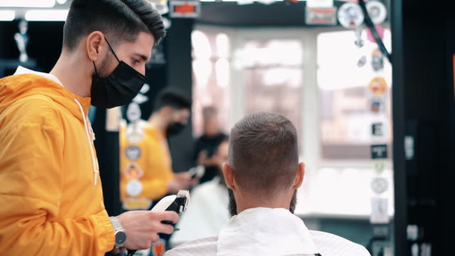 visiting the barber shop during covid-19 - businessman covid mask video stock e b–roll