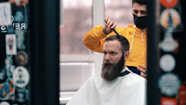 vidéos et rushes de visite du salon de coiffure pendant l'épidémie de covid-19 - coiffeur