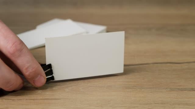 vidéos et rushes de carte blanche blanche vide sur la table en bois. fermez-vous vers le haut. - business card mock up